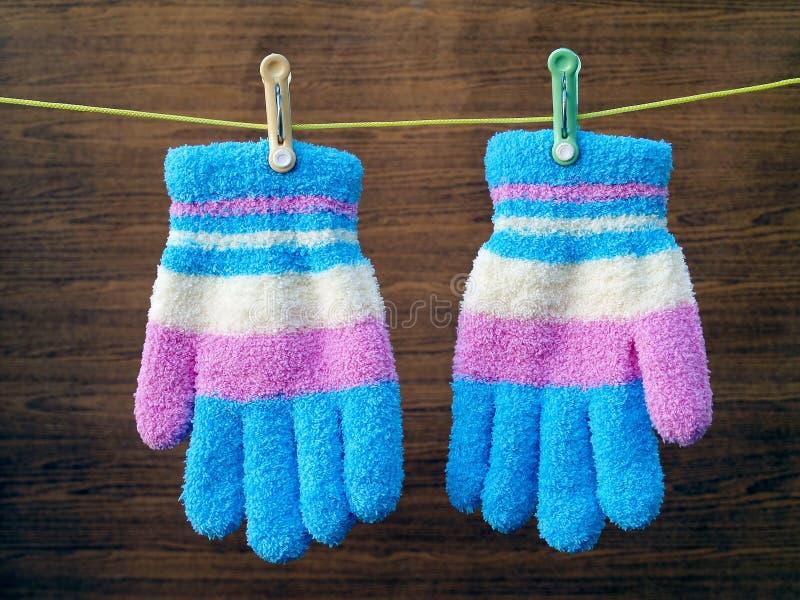 Färgrika vinterhandskar som hänger på en kläderlinje, rope royaltyfri fotografi