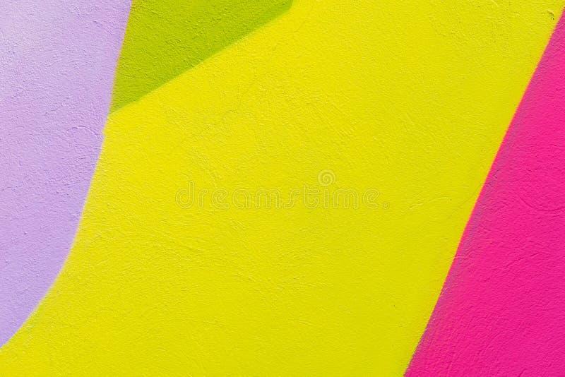 Färgrikt abstrakt begrepp texturerad bakgrund Gatakonst, packad väggfasad med gräsplan, rosa färgen, lilor, guling målar arkivfoton