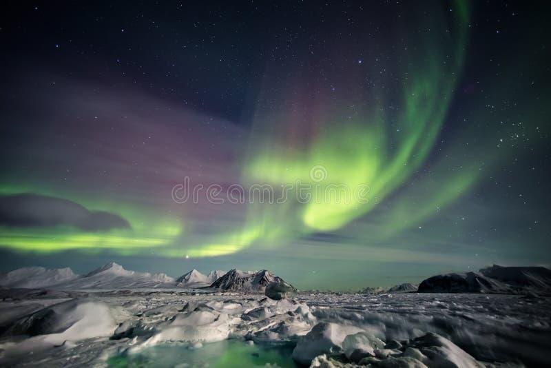 Färgrikt arktiskt vinterlandskap - fryste fjord & nordliga ljus fotografering för bildbyråer