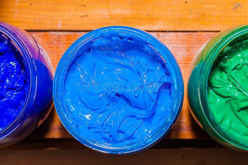 Färgrikt av exponeringsglas för Plastisolfärgpulver kunna utom fara på tallskogtabellen för skjorta för utslagsplats för skärmtry royaltyfria foton