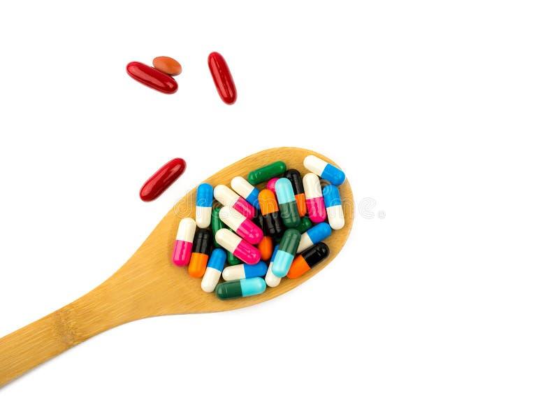 Färgrikt av kapselpreventivpillerar i träsked spiller isolerade på vit bakgrund med kopieringsutrymme och den snabba banan arkivfoto