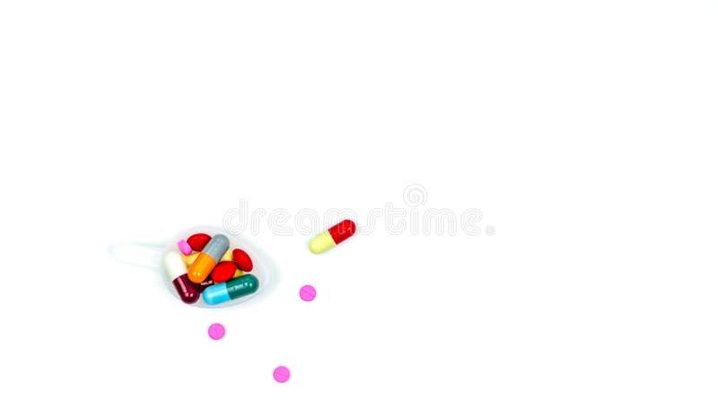 Färgrikt av minnestavlor och kapselpreventivpillerar i plast- tesked och några av dem som är spridda på vit bakgrund med kopierin royaltyfri fotografi