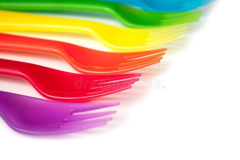 färgrikt behandla som ett barn plast- gafflar på vit bakgrund royaltyfri foto