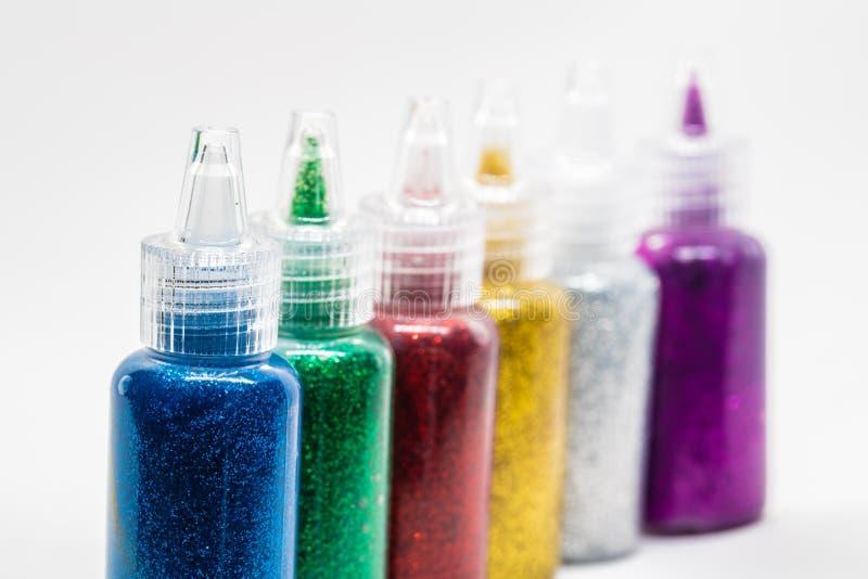 Färgrikt blänka limflaskor arkivfoto