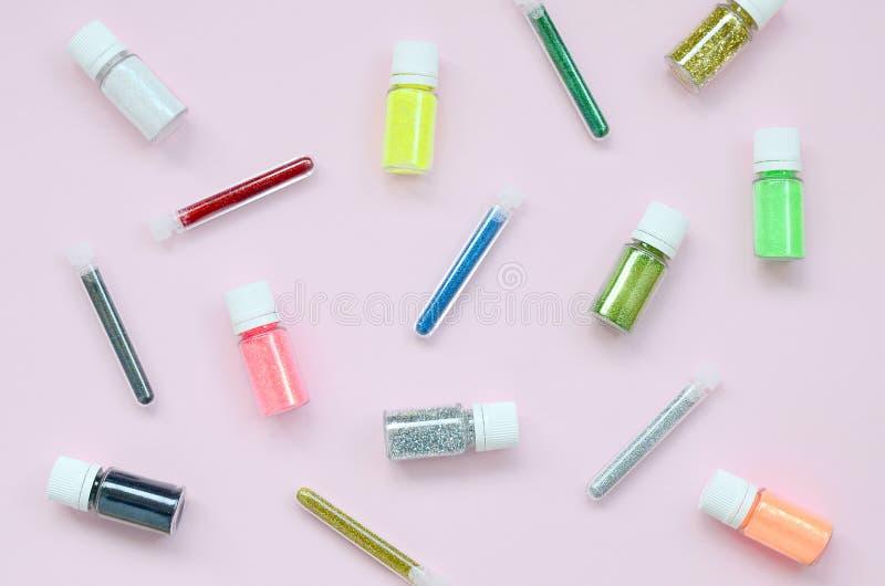 Färgrikt blänker lögner på pastellfärgad rosa bakgrund Många runda krus med mång--färgat ljust mousserar för spikar polermedel arkivbild