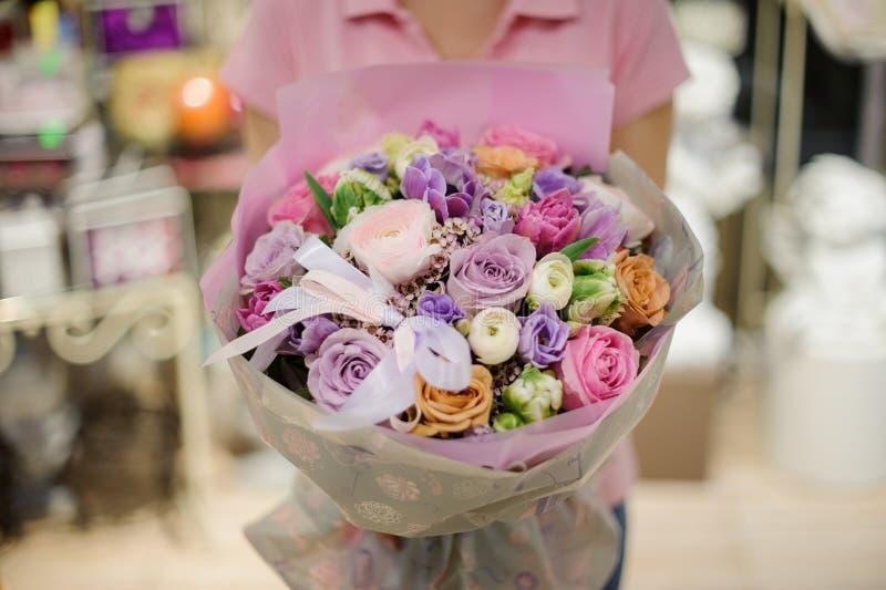 Färgrikt blomsterhandlareinnehav och mjuk blommasammansättning som består av rosor, ranunculus och andra härliga blommor arkivfoton