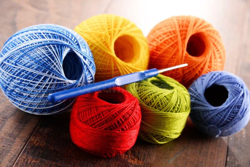 Färgrikt garn för att virka och krok på trätabellen arkivbild