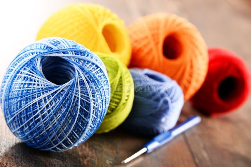 Färgrikt garn för att virka och krok på trätabellen arkivfoton