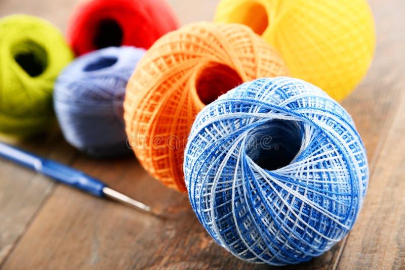 Färgrikt garn för att virka och krok på trätabellen royaltyfri foto