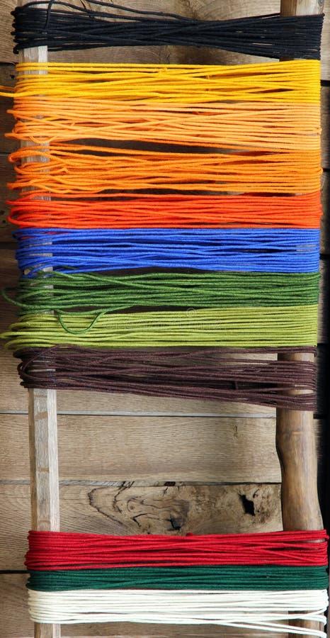 Färgrikt garn på en bakgrund av träväggen arkivfoton