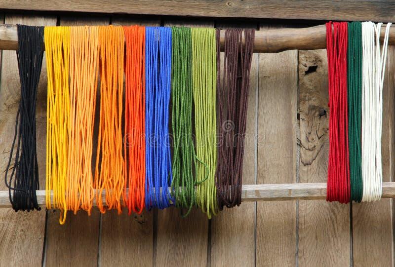 Färgrikt garn på en bakgrund av träväggen royaltyfri fotografi