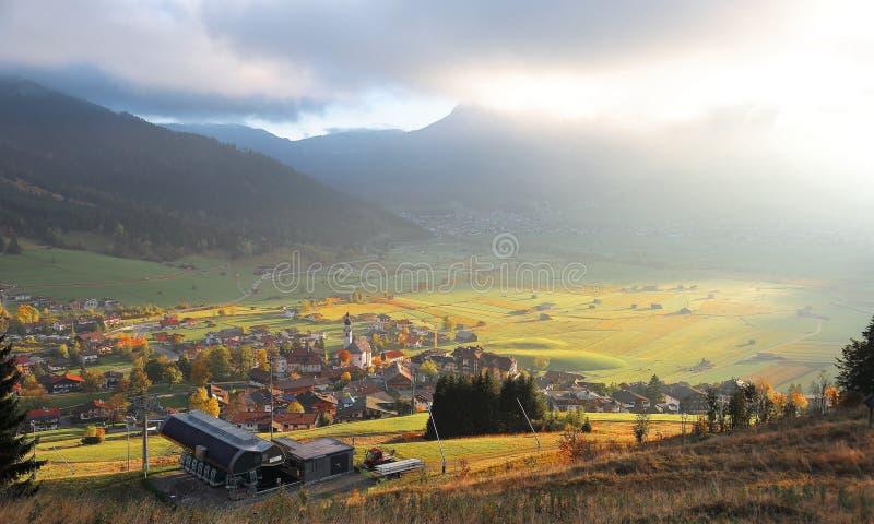 Färgrikt höstlandskap av Lermoos, en Tyrolean by på gräsplanfält badade i guld- solljus royaltyfria bilder