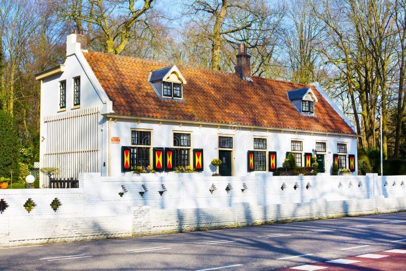 Färgrikt holländskt hus med taket för röd tegelplatta i Holland arkivfoto