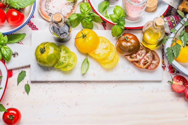 Färgrikt laga mat för tomater Ljusa tomatsalladingredienser på den vita marmorskärbrädan och vit träbakgrund, bästa sikt arkivfoto