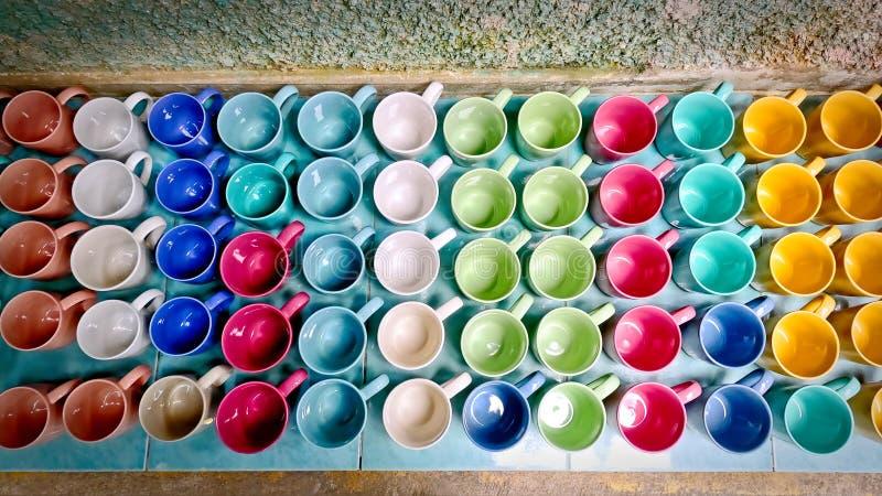 Färgrikt livligt keramiskt kaffe rånar på Sale på det belade med tegel golvet arkivbilder