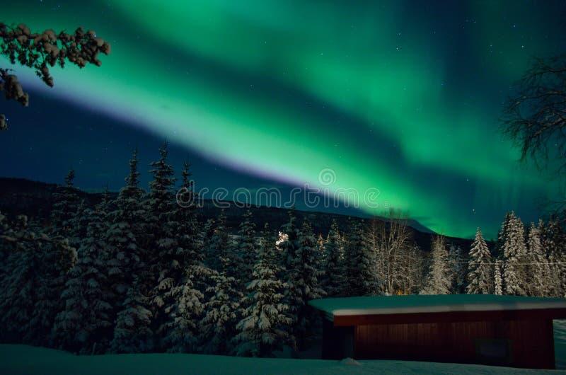 Färgrikt norrsken över berget, skog och garage arkivbilder