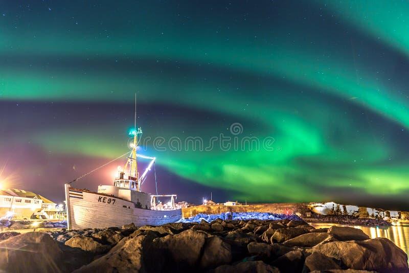 Färgrikt norrsken för nordliga ljus med ett fartyg i förgrunden i Island royaltyfria bilder
