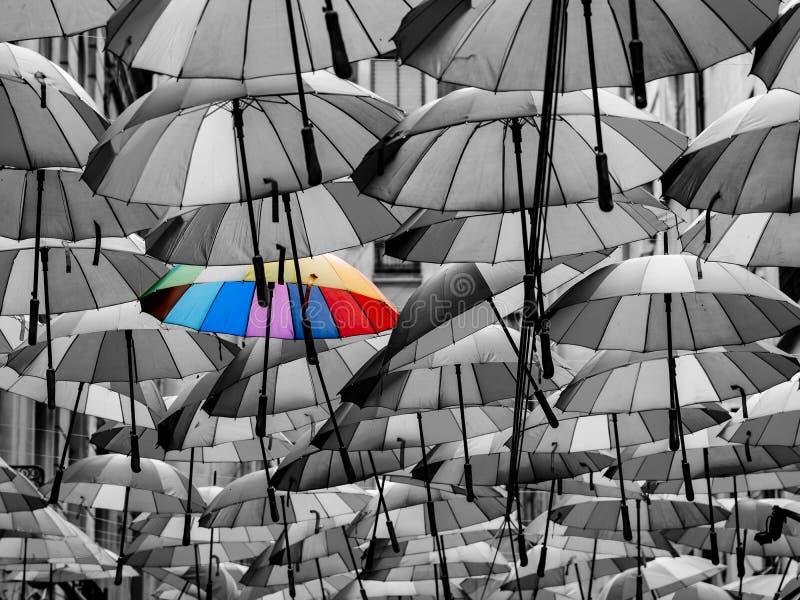Färgrikt paraply bland andra som är olika från folkmassan arkivbilder