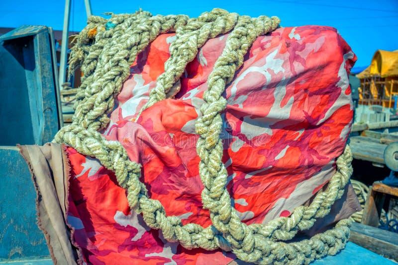 Färgrikt presenningmaterial och gammalt tjockt rep arkivfoto