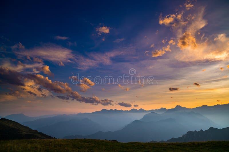Färgrikt solljus på de majestätiska bergmaxima, gräsplan betar och dimmiga dalar av de italienska fjällängarna Guld- cloudscape p royaltyfria bilder