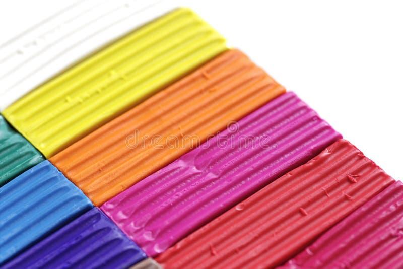 Färgrikt stycke av plasticine eller modelleralera på vit bakgrund Regnbågeuppsättning för barnlek royaltyfria foton