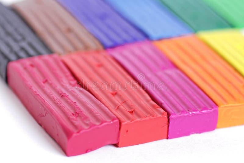 Färgrikt stycke av plasticine eller modelleralera på vit bakgrund Regnbågeuppsättning för barnlek fotografering för bildbyråer