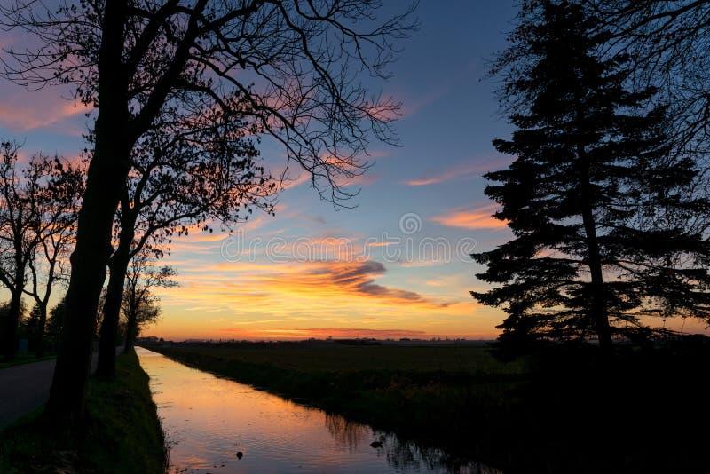 Färgrikt unset över Holland Molnen reflekteras i kanalen, konturerna av träden står ut mot himlen royaltyfria foton