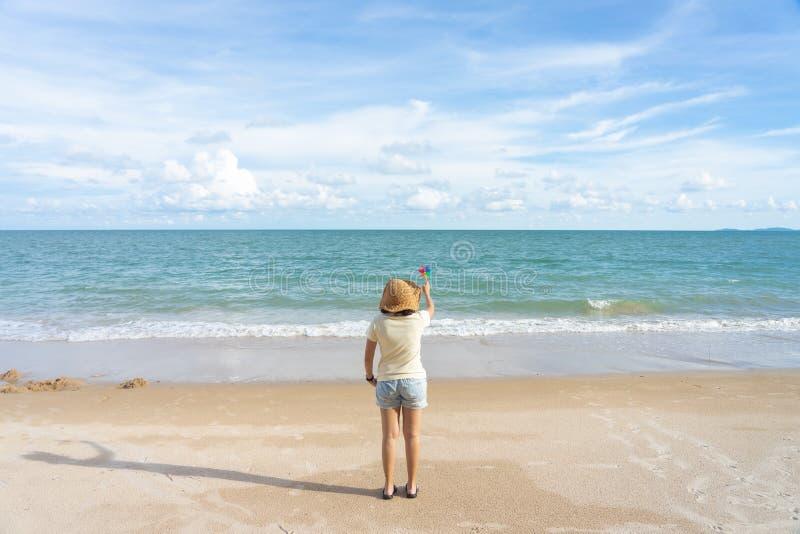 Färgrikt väderkvarnpapper som broderas på strandhavssikten i dagen med en blå bakgrund sommar f?r sn?ckskal f?r sand f?r bakgrund fotografering för bildbyråer