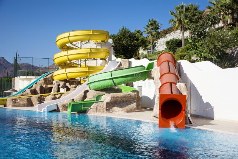 Färgrikt vatten parkerar rör och en simbassäng royaltyfri bild