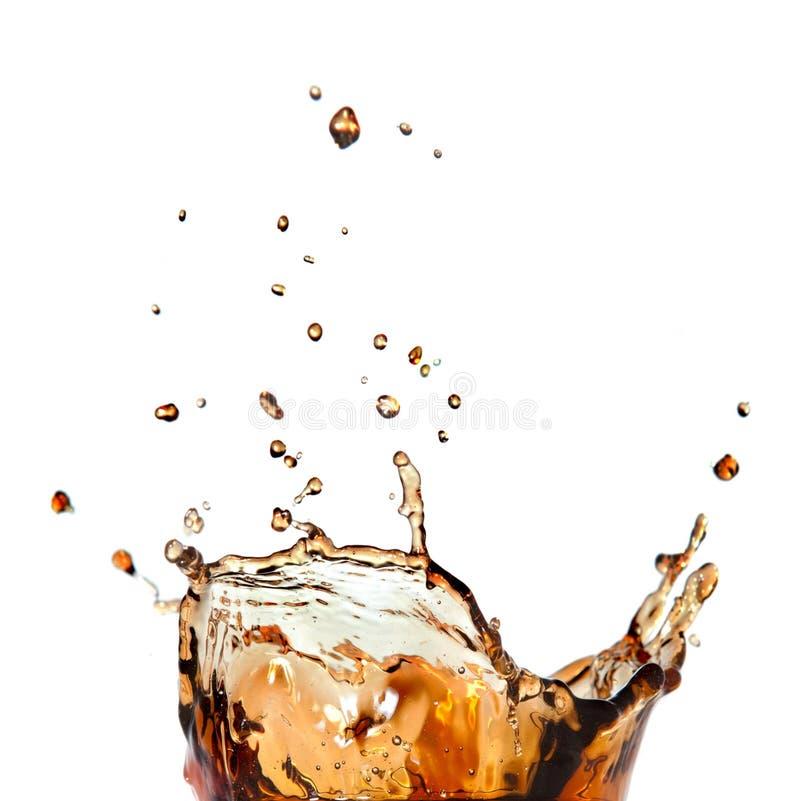 Färgstänk av cola i exponeringsglas som isoleras på vit arkivbild