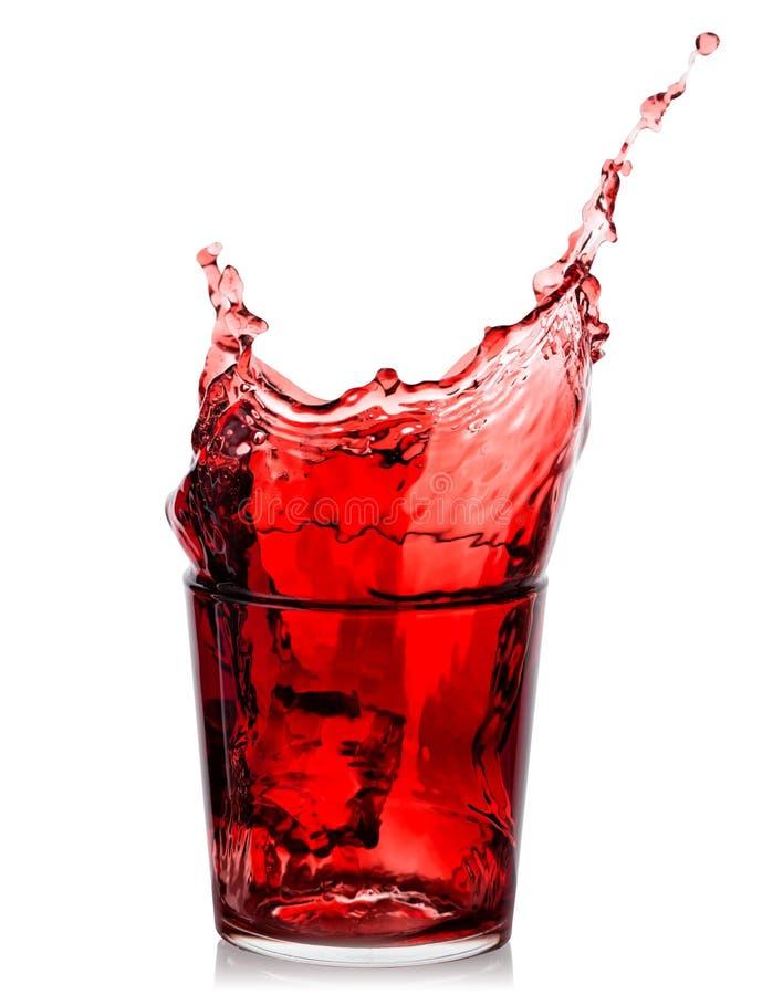 Färgstänk av körsbärsröd fruktsaft i lågt exponeringsglas royaltyfri bild