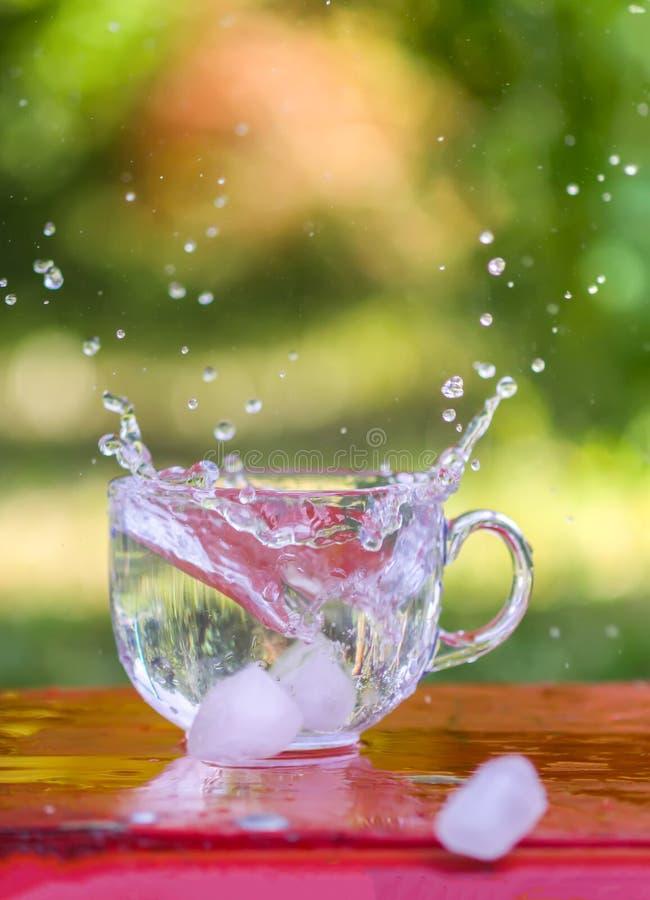 Färgstänk av kall sötvatten med iskuben i genomskinlig exponeringsglaskopp i tabelloutoorsna i sommardag royaltyfria foton