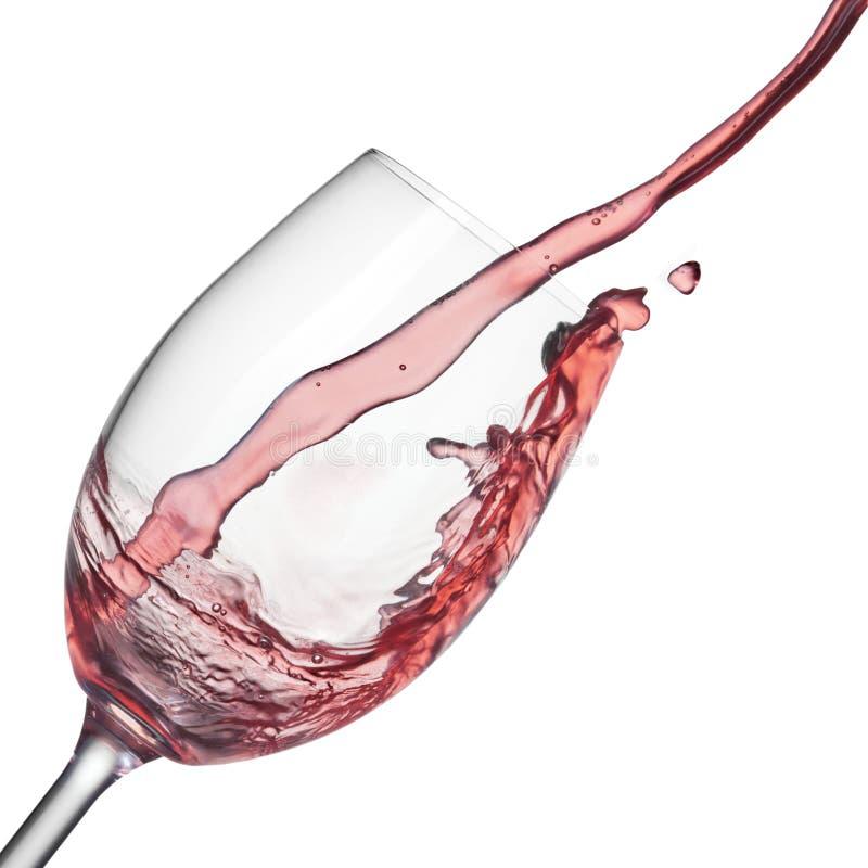 Färgstänk av rosa vin i vinglas på vit royaltyfri fotografi