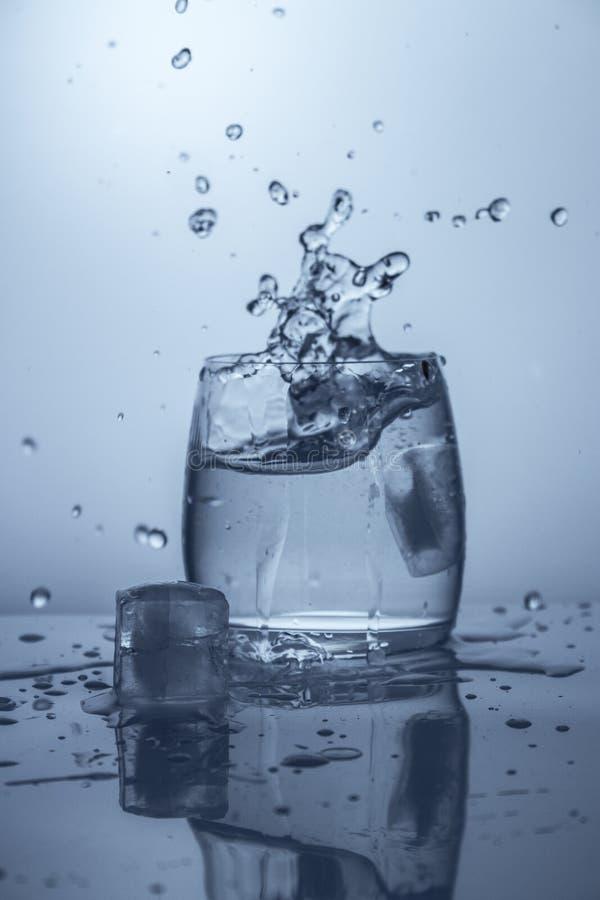 Färgstänk av vatten som plaskar det fallande stycket av is royaltyfri bild
