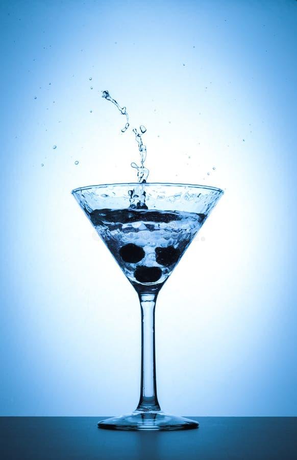 Färgstänk för coctailmartini exponeringsglas på vit och blå lutningbakgrund royaltyfria bilder