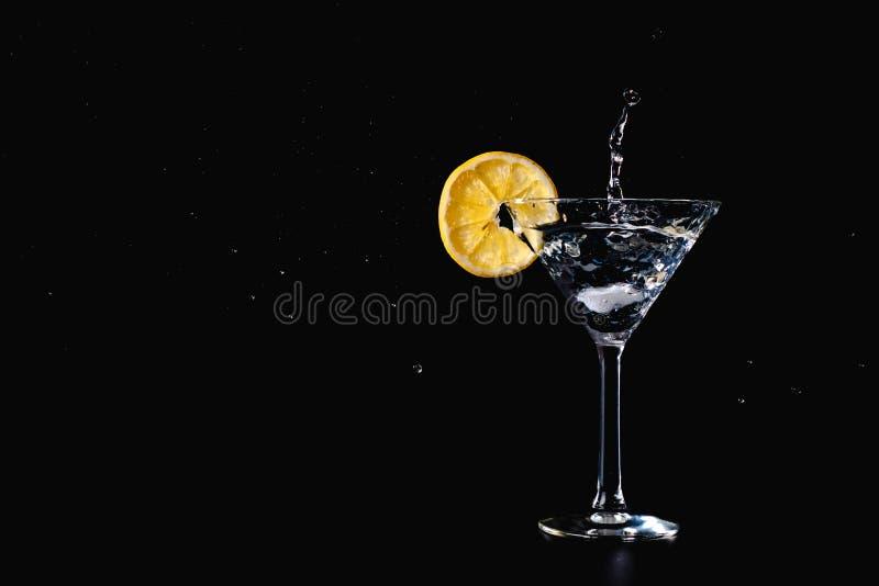 Färgstänk för coctailvattendrink i exponeringsglaset med citronen som isoleras på svart arkivbilder