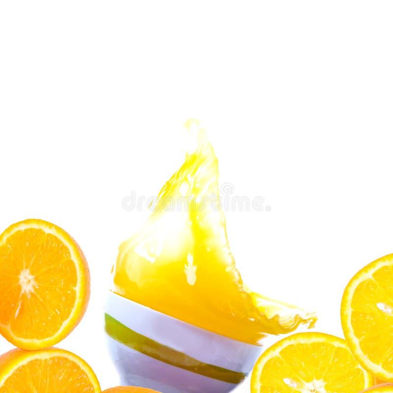Färgstänk för orange fruktsaft i en kopp på en vit bakgrund royaltyfri fotografi