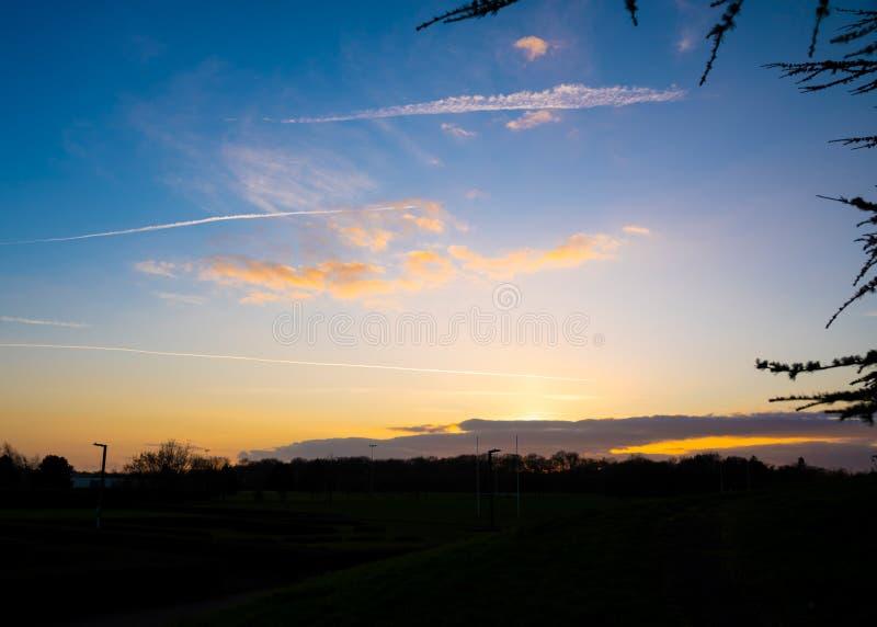 Färgstarka solnedgång med fina moln över skogen på vintern i Milton Keynes royaltyfria bilder