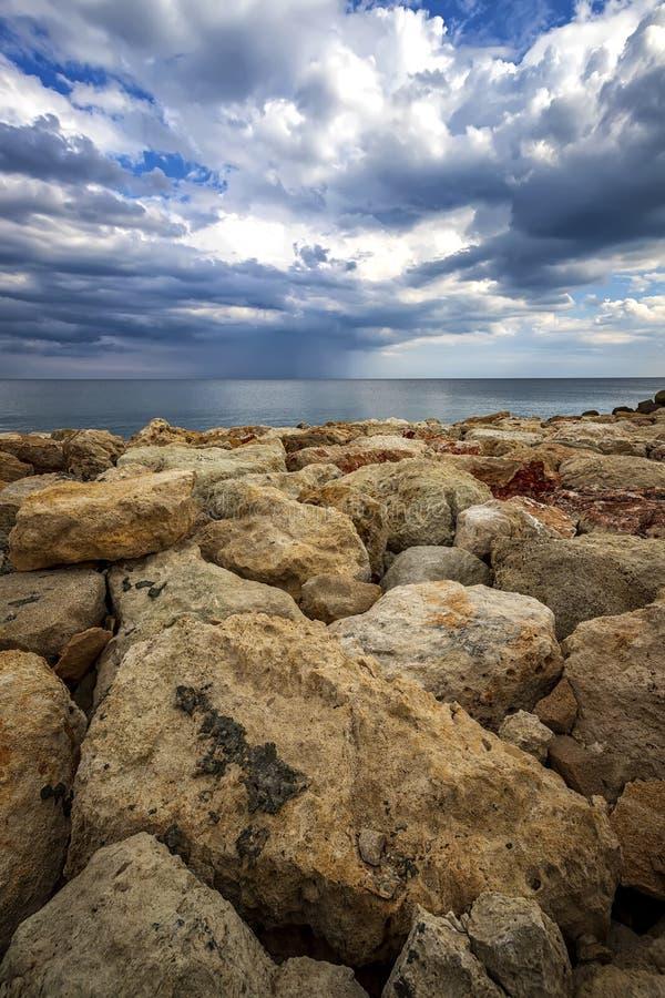 Färgstenar på en strand med stormiga moln vid horisonten royaltyfri foto