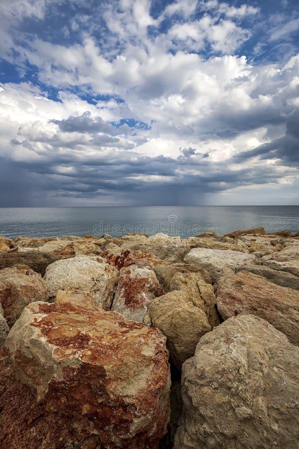 Färgstenar på en strand med stormiga moln vid horisonten royaltyfri bild