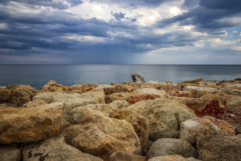 Färgstenar på en strand med stormiga moln vid horisonten arkivfoto