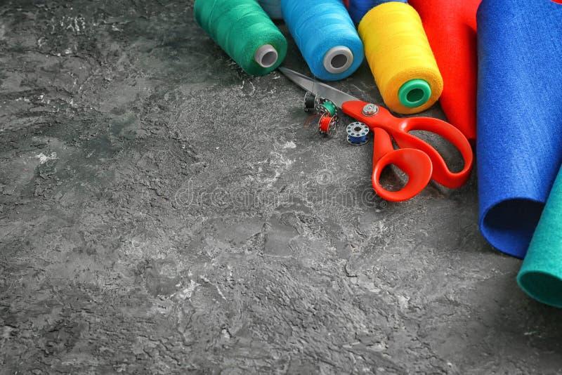 Färgtrådar med tyg och sax på mörk texturerad bakgrund royaltyfria bilder