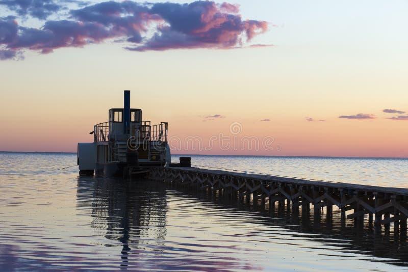 Färja nära pir på solnedgången royaltyfri fotografi
