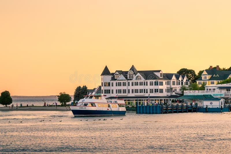 Färja som lämnar hamnen, medan den i stadens centrum Mackinac ön sitter bak den på solnedgången royaltyfri fotografi