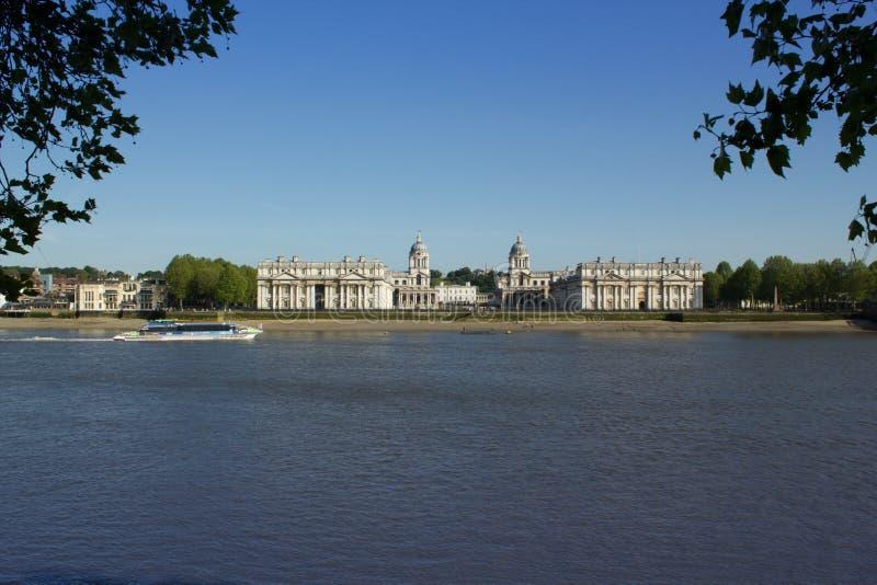 Färja som passerar den gamla kungliga sjö- högskolan i Themsen på Greenwich, England arkivbilder