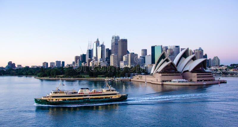 Färjan passerar framme av Sidney Opera House med staden i bakgrunden royaltyfri foto