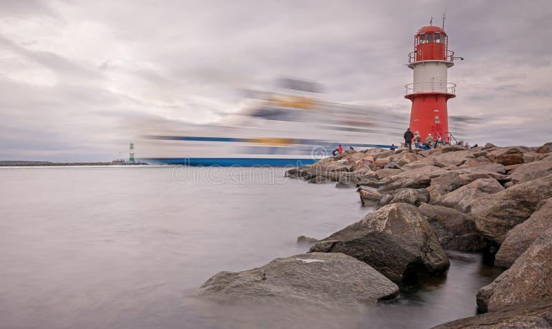 Färjefartyget passerar ljusfyren vid hamnen Rostock-Warnemünde royaltyfria foton