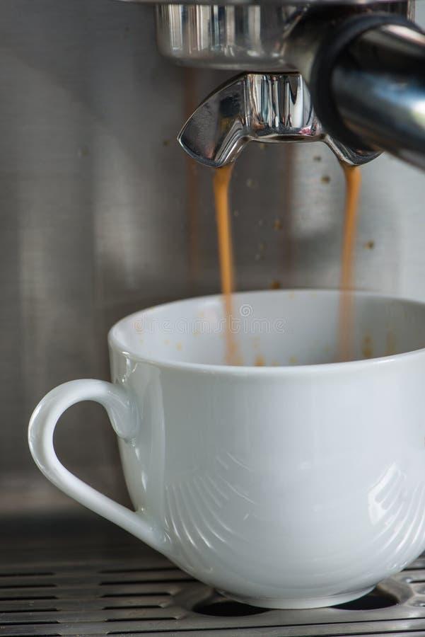 Färsk Espresso som hälls i vit bägare royaltyfria foton