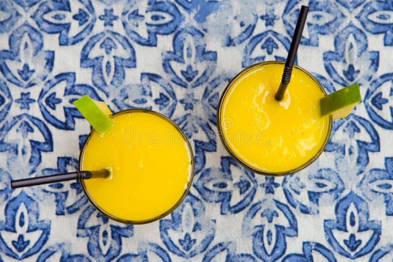 Färsk mango smoothie, saft på blå bakgrund Överkant arkivbilder