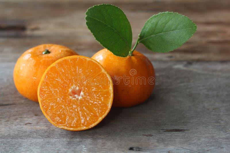 Färska apelsiner och en halv på träplattan royaltyfria bilder